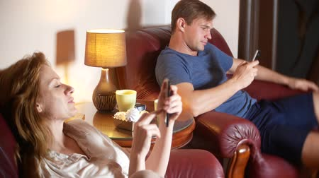 disinterest : Internal and communication problem in the family. husband and wife use their smartphone, ignoring each other. 4k.