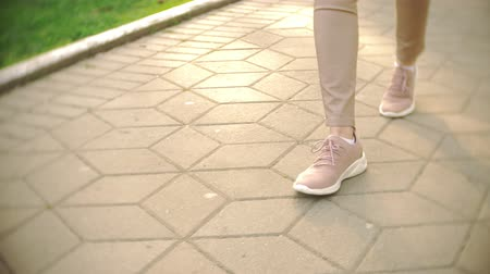 paving : thin womens legs in beige trousers and sneakers stroll in the park on a clear sunny day. 4k, slow motion