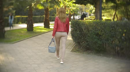 умник : the camera follows the blonde girl. a woman in a red jacket strolls through the city park on a clear sunny day. 4k, slow motion Стоковые видеозаписи