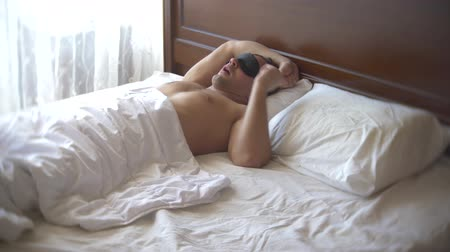 acorde : Young man in a mask for sleeping, sleeping in bed on a pillow in the daytime. 4k. Stock Footage