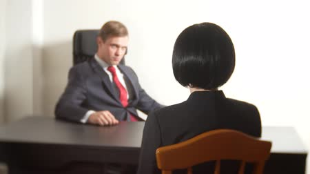 recrutamento : a man in a suit asks questions to a brunette woman in an interview. 4k. interview. recruitment Vídeos