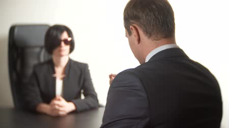 recrutamento : a brunette woman in a suit asks questions to a man in an interview. 4k. interview. recruitment