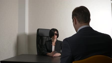 enrollment : a brunette woman in a suit asks questions to a man in an interview. 4k. interview. recruitment
