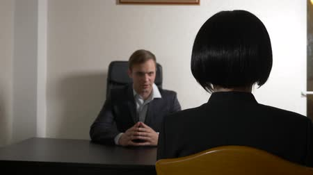 enrollment : a man in a suit asks questions to a brunette woman in an interview. 4k. interview. recruitment Stock Footage