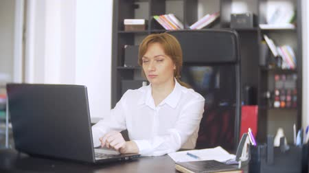 босс : woman working in office with documents and laptop. she looks at the camera and smiles 4k.