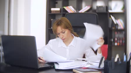 множество : a businesswoman who scans documents, frowns, using a laptop, does not perform an urgent task in the office, there is not enough time, 4k. the office is hot, the air conditioning is not working Стоковые видеозаписи