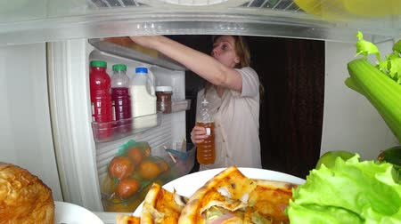 bulimia : Woman opens the refrigerator at night. night hunger. diet. gluttony, 4k Stock Footage