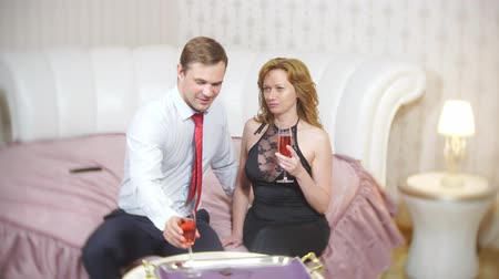 nowożeńcy : Couple drinking wine on the bed. an elegant couple, a man in a suit and a woman in an evening gown are drinking wine in the luxurious hotel room on the bed. 4k