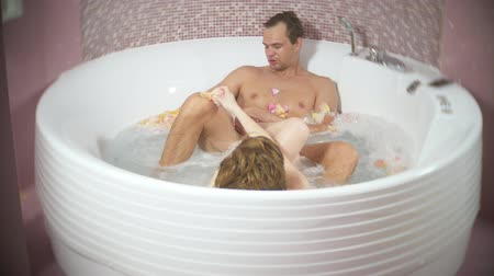 купаться : attractive couple man and woman in a round bathroom with rose petals and foam, enjoying bubbling water, hugging and kissing. a man kisses a womans feet, foot fetish 4k.