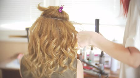 bodorítás : Hair stylist makes a curls for a girl, using hair styling. Hairdresser at work. 4k