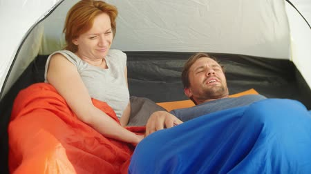прижиматься : Closeup. A cute couple hugging inside a tent lying in sleeping bags, they flirt and kiss, 4k.