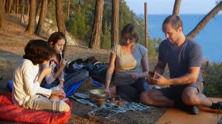 baharatlı alman sosisi : a happy family of tourists, eating camp food, next to a tent on the edge of a steep coastline in a pine grove with a magnificent view of the seascape. 4k.