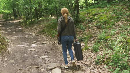 sigilo : girl, walks through the woods with a heavy black suitcase. 4k, slow-motion shooting, steadicam shot. Stock Footage