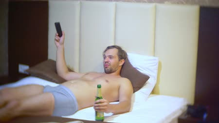 молодой взрослый человек : Man watching tv and drinking beer At home on a bed. 4k