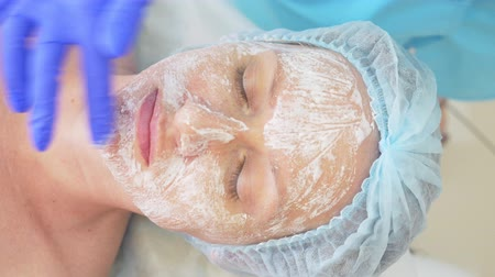 omlazení : Close up of beauty procedure. Beautician cleaning facial mask. Peeling. Beauty and body skin care. slow motion 4k