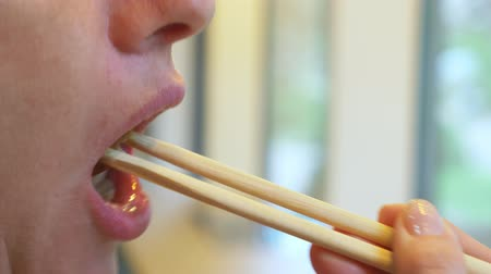 kaviár : Young woman in cafe eating sushi with chopsticks. 4k, close-up. Stock mozgókép