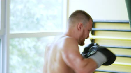 zajosan rágcsál : a professional sportsman a boxer trains in the martial arts hall. young European man in the gym. 4k,