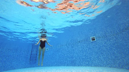 akciók : 4k. View under water. Woman in a black swimsuit Swims in the pool.