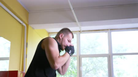 champ : A professional boxer athlete trains in the martial arts hall. young European man in the gym, wearing a T-shirt with an inscription coach. 4k, slow-motion,