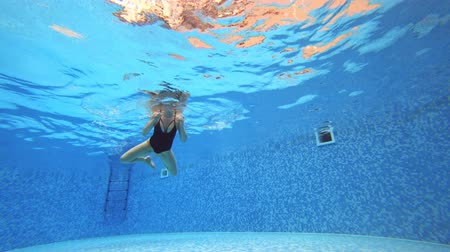 without face : 4k. View under water. Woman in a black swimsuit Swims in the pool.