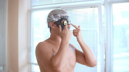 урод : Strange man with face pack. A young man does cosmetic procedures for the face of a house in front of a mirror. 4k, cucumber mask