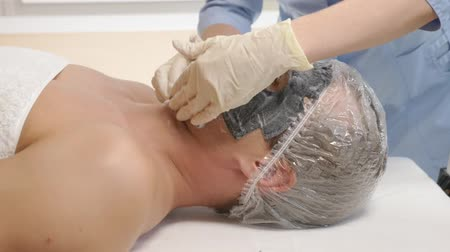 masaj : Spa therapy for handsome men receiving facial mask. 4k. Slow motion. Reception of a cosmetologist