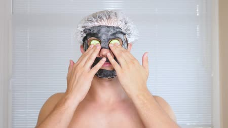 eye mask : Strange man with face pack. A young man does cosmetic procedures for the face of a house in front of a mirror. 4k, cucumber mask