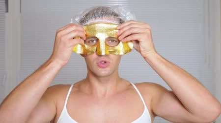 урод : Strange man with face pack. A young man does cosmetic procedures for the face of a house in front of a mirror. 4k