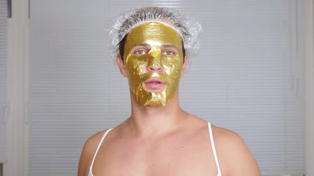 урод : Strange man with face pack. A young man does cosmetic procedures for the face of a house in front of a mirror. 4k, golden mask Стоковые видеозаписи