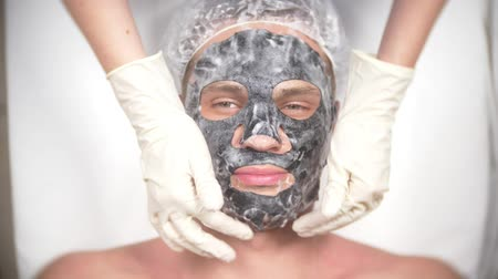 lateks : Spa therapy for handsome men receiving facial mask. 4k. Slow motion. Reception of a cosmetologist