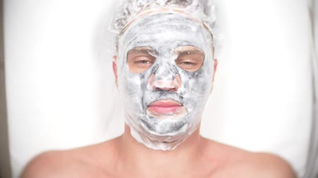 bőrgyógyászat : Spa therapy for handsome men receiving facial mask. 4k. Slow motion. Reception of a cosmetologist