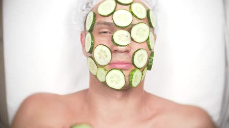 zvláštní : Strange man with face pack. A young man does cosmetic procedures for the face of a house in front of a mirror. 4k, cucumber mask