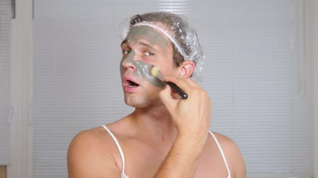 странный : Strange man with face pack. A young man does cosmetic procedures for the face of a house in front of a mirror. 4k
