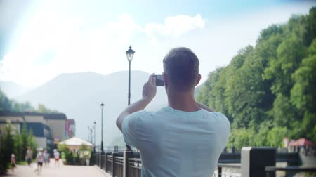 oneperson : man using smartphone walking in the city on a hot sunny day. Travel. The concept of a way of life. gadget of modern communication technology. 4k, slow motion