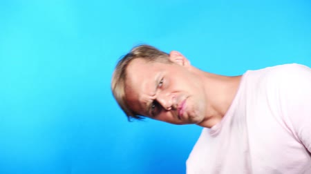 здесь : Young man on a colored blue background. portrait. emotions and gestures. 4k, close-up. Slow motion. the guy looks in the camera with interest. whats happening .