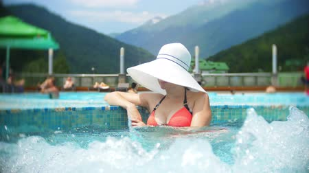 болваны : SLOW MOTION, CLOSE, PORTRAIT. young woman in a big white hat, sunbathe and relax on a sunny day in a luxurious pool on a background of a mountain landscape. mountain resort with outdoor pool. 4k