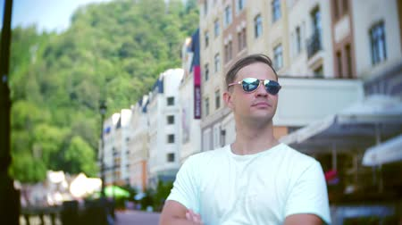 keskeny kilátás : young stylish man, posing on city streets. on a hot summer day. he looks at the camera and smiles. 4k, slow-motion, close-up. Stock mozgókép