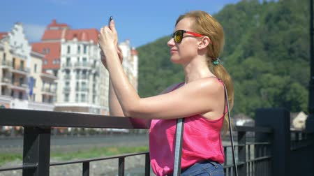 oneperson : Woman using smartphone walking in the city on a hot sunny day. Travel. The concept of a way of life. gadget of modern communication technology. 4k, slow motion