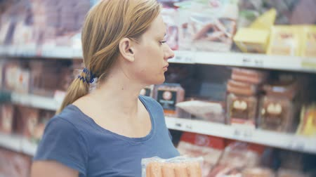 супермаркет : woman buys a sausage in a supermarket, 4k Стоковые видеозаписи
