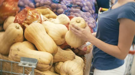 fresh produce : A woman in a supermarket buying vegetables, pumpkin Stock Footage