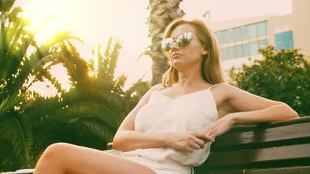 glare : Beautiful stylish blond woman in sunglasses , walking along a palm tree path. The palm is reflected in the glasses. 4K slow motion.