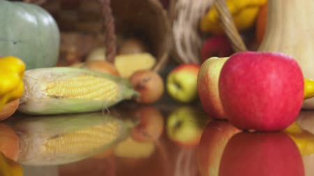 hasır : Autumnal Harvest or Thanksgiving, Cornucopia filled with vegetables, vegetables spilled out of the basket on the table. 4k, dolly shot