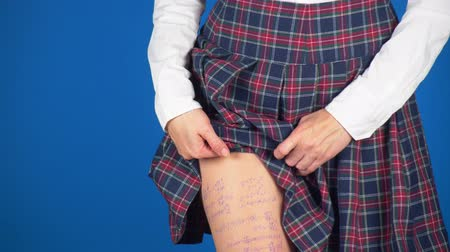 cheat : Midsection of teenage girl, cheat sheet written on hips hidden under a skirt. 4k, close-up, blue background, slow-motion shooting.