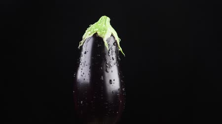warzywa : eggplant, close - up. Drops of water fall on a rotating apple on a black background. super slow-motion.