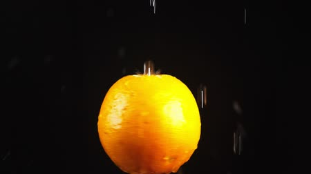 mandarinka : orange, close - up. Drops of water fall on a rotating apple on a black background. super slow-motion.