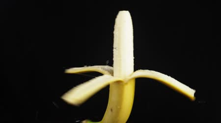 spraying : peeled banana , close - up. Drops of water fall on a rotating apple on a black background. super slow-motion.