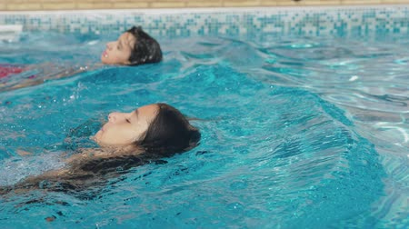 dvojčata : Two happy teenagers, a brother and sister, are swimming in a race in the pool. Slow motion. steadicam shot. 4k