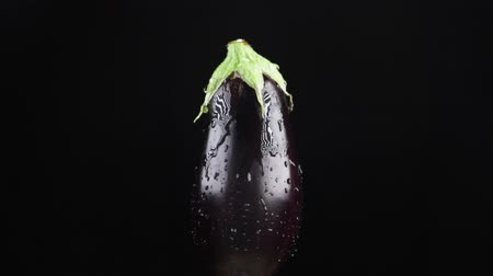 beringela : eggplant, close - up. Drops of water fall on a rotating apple on a black background. super slow-motion.