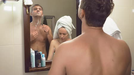 escova de dentes : beautiful couple, man and woman, wash together in the bathroom in front of the mirror. 4k, slow motion, The woman takes the razor from her husband and starts shaving her armpits Stock Footage