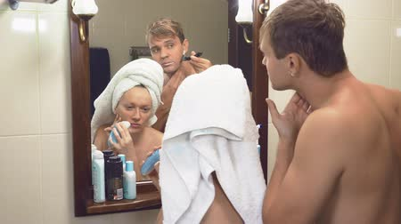 teeth brushing : beautiful couple, man and woman, wash together in the bathroom in front of the mirror. 4k, slow motion, the husband shaves his face with a machine tool, a woman makes a epilation of the hair on her face with a depilation machine Stock Footage